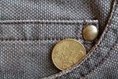 Euromünze mit einer Bezeichnung von 10 Eurocents in der Tasche von abgenutzten braunen Denimjeans Stockbild