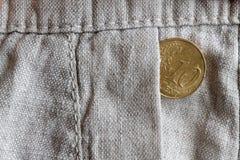Euromünze mit einer Bezeichnung von 10 Eurocents in der Tasche der alten Leinenhose Lizenzfreie Stockbilder
