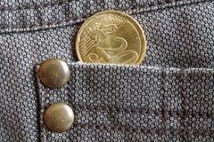 Euromünze mit einer Bezeichnung von 20 Eurocents in der Tasche von braunen Denimjeans Lizenzfreies Stockfoto