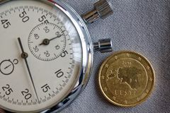 Euromünze mit einer Bezeichnung von 50 Eurocents (Rückseite) und von Stoppuhr auf grauem Denimhintergrund - Geschäftshintergrund Lizenzfreie Stockfotografie