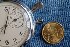 Euromünze mit einer Bezeichnung von 20 Eurocents und von Stoppuhr auf abgenutztem blauem Denimhintergrund - Geschäftshintergrund Lizenzfreie Stockfotografie