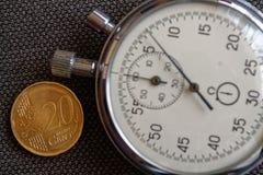 Euromünze mit einer Bezeichnung von 20 Eurocents und von Stoppuhr auf braunem Denimhintergrund - Geschäftshintergrund Lizenzfreie Stockbilder