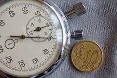 Euromünze mit einer Bezeichnung von 10 Eurocents und von Stoppuhr auf grauem Denimhintergrund - Geschäftshintergrund Lizenzfreies Stockfoto