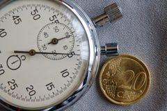 Euromünze mit einer Bezeichnung von 20 Eurocents und von Stoppuhr auf grauem Denimhintergrund - Geschäftshintergrund Stockfotografie