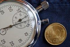 Euromünze mit einer Bezeichnung von 20 Eurocents und von Stoppuhr auf veraltetem blauem Denimhintergrund - Geschäftshintergrund Lizenzfreies Stockfoto