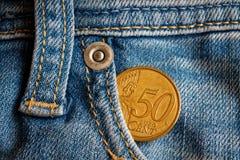 Euromünze mit einer Bezeichnung von fünfzig Eurocents in der Tasche von abgenutzten hellblauen Denimjeans Stockfotos