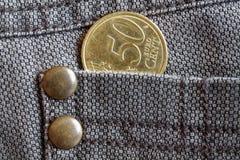 Euromünze mit einer Bezeichnung von fünfzig Eurocents in der Tasche von braunen Denimjeans Lizenzfreies Stockbild