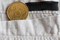 Euromünze mit einer Bezeichnung von fünfzig Eurocents in der Tasche der Leinenhose mit schwarzem Streifen Lizenzfreie Stockbilder