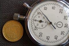 Euromünze mit einer Bezeichnung von fünfzig Eurocents (Rückseite) und von Stoppuhr auf braunem Denimhintergrund - Geschäftshinter Stockfotografie