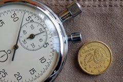 Euromünze mit einer Bezeichnung von zehn Eurocents (Rückseite) und von Stoppuhr auf altem beige Jeanshintergrund - Geschäftshinte Lizenzfreie Stockbilder