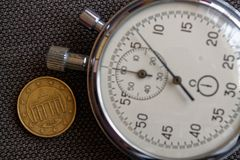 Euromünze mit einer Bezeichnung von zehn Eurocents (Rückseite) und von Stoppuhr auf braunem Denimhintergrund - Geschäftshintergru Lizenzfreies Stockfoto