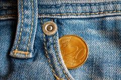 Euromünze mit einer Bezeichnung von zwanzig Eurocents in der Tasche von abgenutzten hellblauen Denimjeans Lizenzfreie Stockbilder