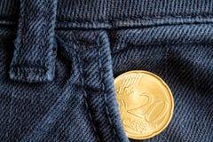 Euromünze mit einer Bezeichnung von zwanzig Eurocents in der Tasche von alten blauen Denimjeans Lizenzfreies Stockbild