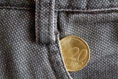 Euromünze mit einer Bezeichnung von zwanzig Eurocents in der Tasche von alten braunen Denimjeans Lizenzfreie Stockbilder