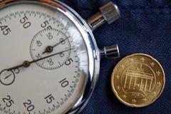 Euromünze mit einer Bezeichnung von zwanzig Eurocents (Rückseite) und von Stoppuhr auf abgenutztem Blue Jeans-Hintergrund - Gesch Lizenzfreie Stockfotos