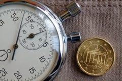 Euromünze mit einer Bezeichnung von zwanzig Eurocents (Rückseite) und von Stoppuhr auf altem beige Jeanshintergrund - Geschäftshi Stockbild