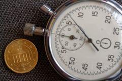Euromünze mit einer Bezeichnung von zwanzig Eurocents (Rückseite) und von Stoppuhr auf braunem Denimhintergrund - Geschäftshinter Lizenzfreie Stockbilder