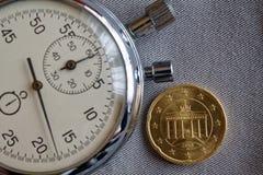 Euromünze mit einer Bezeichnung von zwanzig Eurocents (Rückseite) und von Stoppuhr auf grauem Denimhintergrund - Geschäftshinterg Stockbild