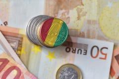 Euromünze mit Staatsflagge der Guine auf dem Eurogeldbanknotenhintergrund lizenzfreie stockbilder