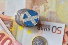 Euromünze mit Staatsflagge von Schottland auf dem Eurogeldbanknotenhintergrund Lizenzfreie Stockbilder