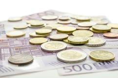 Euromünzen auf 500 Banknoten Stockfotografie