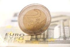 2 Euromünzen auf Banknoten Stockfotos