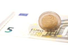 2 Euromünzen auf Banknoten Stockbilder