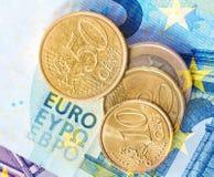 Euromünzen auf Eurobanknotenhintergrund Lizenzfreie Stockfotografie