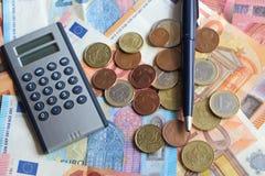Euromünzen, Banknoten, Taschenrechner und Stift stockfoto