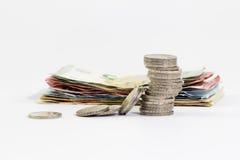 2 Euromünzen gestapelt und Eurobanknoten Stockbild