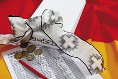 Euromünzen mit Bleistift, Trauerband und Dokument auf deutscher Flagge Stockbild