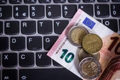 Euromünzen und Banknoten über laptop& x27; s-Tastatur Stockbild