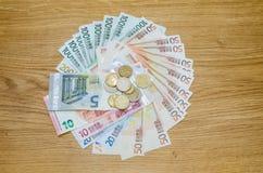 Euromünzen und Banknoten auf Holztisch Lizenzfreie Stockbilder