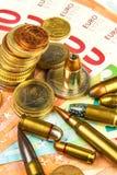 Euromünzen und Banknoten und Patronen des unterschiedlichen Kalibers Illegaler Handel in der Munition Verkauf von Waffen Finanzie lizenzfreie stockbilder