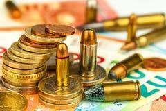 Euromünzen und Banknoten und Patronen des unterschiedlichen Kalibers Illegaler Handel in der Munition Verkauf von Waffen Finanzie lizenzfreie stockfotos