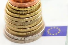 Euromünzen und Eu-Flagge Stockfotografie