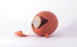 1 Euromünzenverlassen ein gebrochenes ausgebrütetes Ei Stockbilder