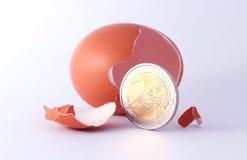 1 Euromünzenverlassen ein gebrochenes ausgebrütetes Ei Stockbild