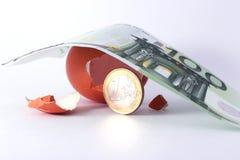 1 Euromünzenverlassen ein gebrochenes ausgebrütetes Ei unter Banknote des Euros 100 Lizenzfreie Stockfotografie