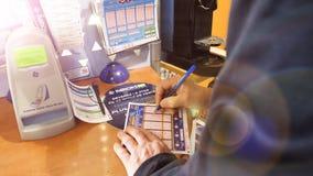 Euromillions del boleto de lotería del terraplén del hombre mayor en quiosco de la prensa del tabak almacen de video
