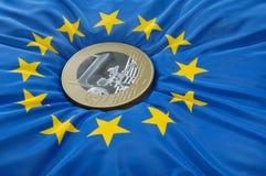 Euromünze auf europäischer Markierungsfahne Stockbilder