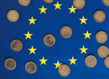 Euromynt, europeisk union, över flagga Arkivfoto