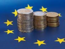 Euromynt, europeisk union, över flagga Arkivfoton