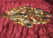 Euromynt, europeisk union över röd sammetbakgrund Arkivbilder