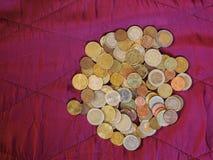 Euromynt, europeisk union över röd sammetbakgrund Arkivfoto