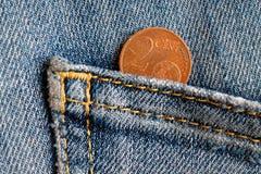 Euromynt med en valör av cent för euro 2 i facket av gammal blå grov bomullstvilljeans Arkivbild