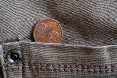 Euromynt med en valör av cent för euro 2 i facket av gammal grå grov bomullstvilljeans Arkivbilder
