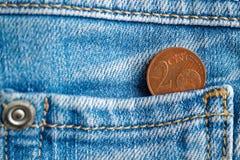 Euromynt med en valör av cent för euro 2 i facket av gammal sliten blå grov bomullstvilljeans Fotografering för Bildbyråer