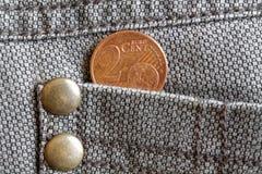 Euromynt med en valör av cent för euro 2 i facket av gammal sliten brun grov bomullstvilljeans Arkivbild