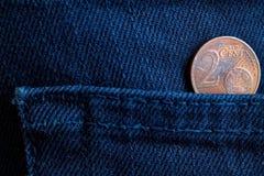 Euromynt med en valör av cent för euro 2 i facket av mörker - blå grov bomullstvilljeans Arkivbild